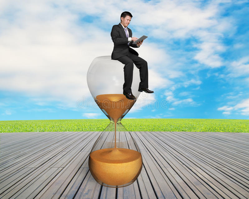 Άτομο που χρησιμοποιεί την έξυπνη συνεδρίαση μαξιλαριών στα sandglass στοκ φωτογραφίες