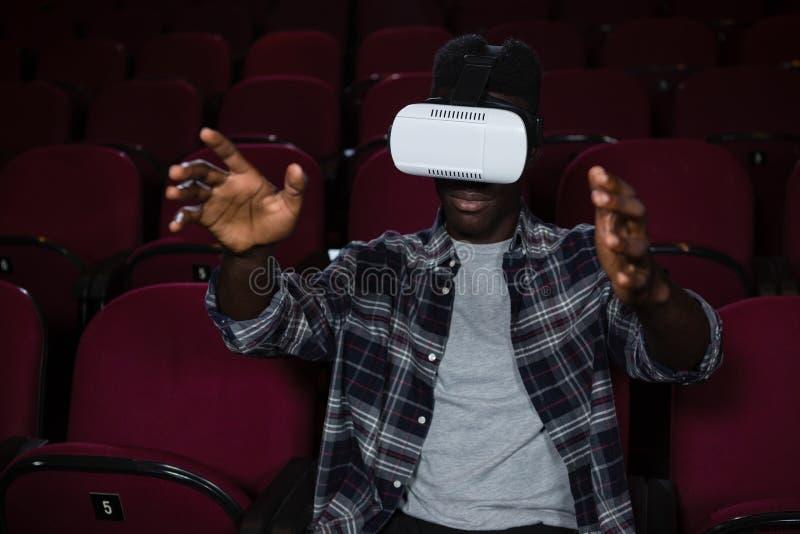 Άτομο που χρησιμοποιεί την κάσκα εικονικής πραγματικότητας προσέχοντας τον κινηματογράφο στοκ εικόνα με δικαίωμα ελεύθερης χρήσης