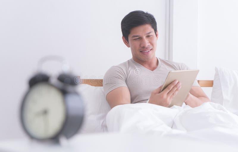 Άτομο που χρησιμοποιεί την ταμπλέτα στο κρεβάτι με το ξυπνητήρι που μετρά αργά στοκ εικόνες με δικαίωμα ελεύθερης χρήσης