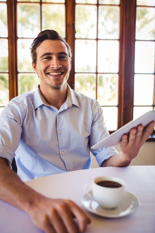 Άτομο που χρησιμοποιεί την ψηφιακή ταμπλέτα ενώ έχοντας τον καφέ στο εστιατόριο στοκ εικόνες