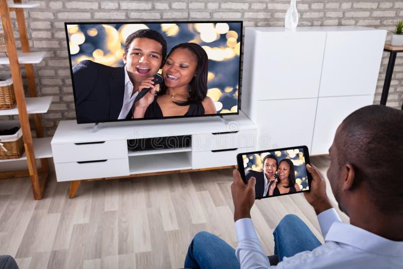 Άτομο που χρησιμοποιεί την ψηφιακή ταμπλέτα προσέχοντας την τηλεόραση στοκ φωτογραφία