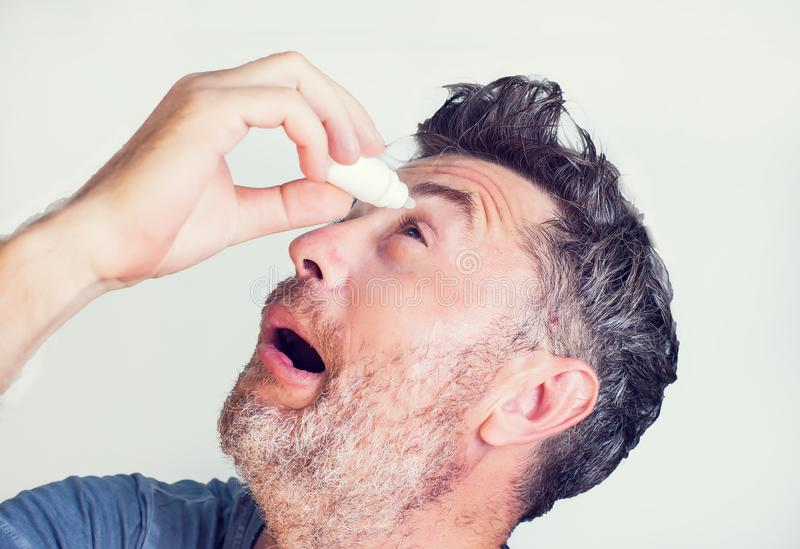 άτομο που χρησιμοποιεί τις πτώσεις ματιών στα μάτια στοκ εικόνες