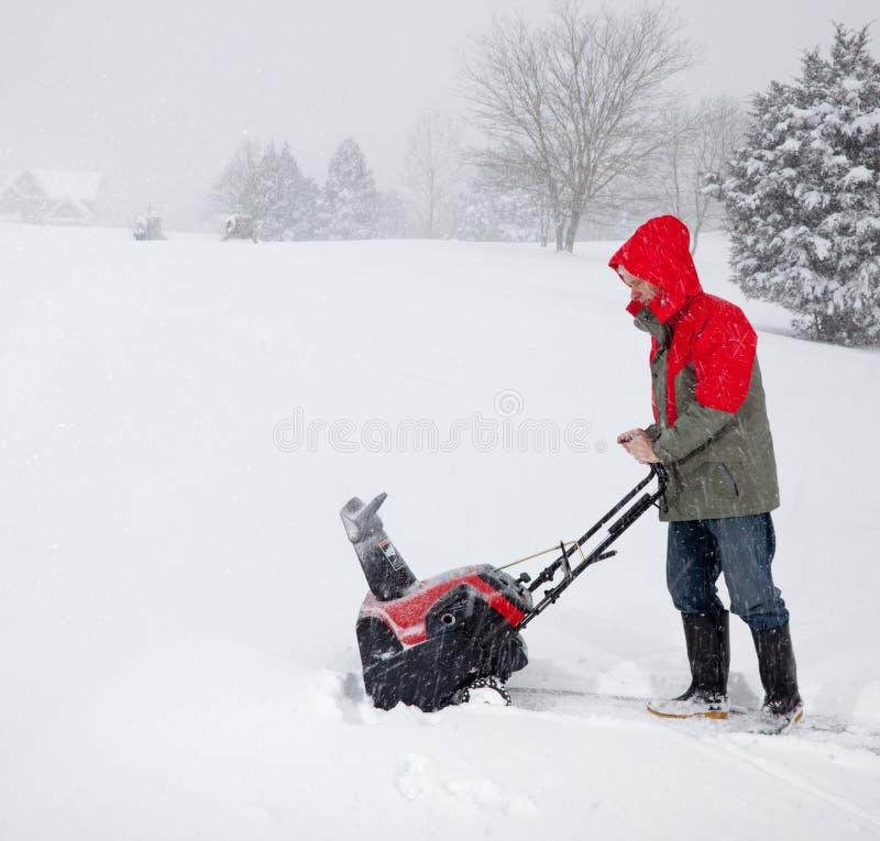 Άτομο που χρησιμοποιεί τον ανεμιστήρα χιονιού στο χιονώδη ρυθμιστή στοκ φωτογραφία