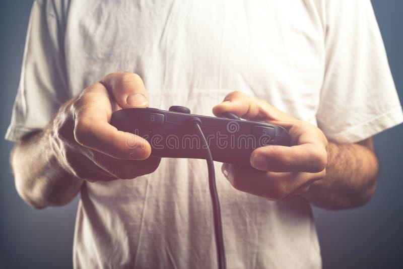 Άτομο που χρησιμοποιεί τον ελεγκτή μαξιλαριών παιχνιδιών για να παίξει τα τηλεοπτικά παιχνίδια στοκ εικόνα με δικαίωμα ελεύθερης χρήσης