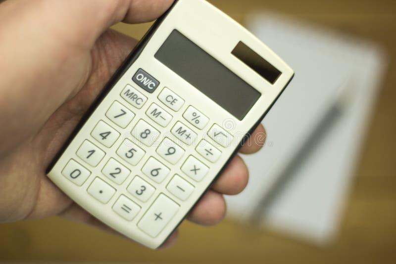 Άτομο που χρησιμοποιεί τον υπολογιστή για να μετρήσει το εισόδημα και την έκβαση στοκ εικόνες