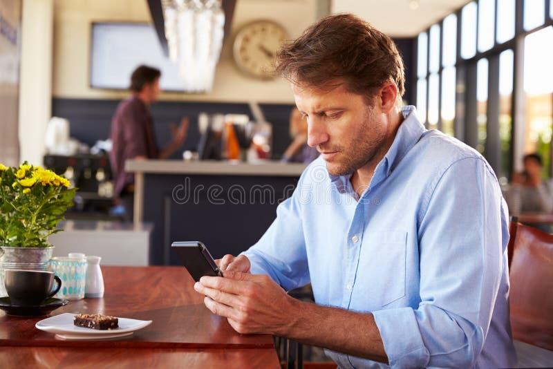 Άτομο που χρησιμοποιεί το έξυπνο τηλέφωνο σε μια καφετερία στοκ εικόνα