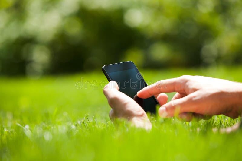 Άτομο που χρησιμοποιεί το κινητό έξυπνο τηλέφωνο υπαίθριο στοκ φωτογραφίες