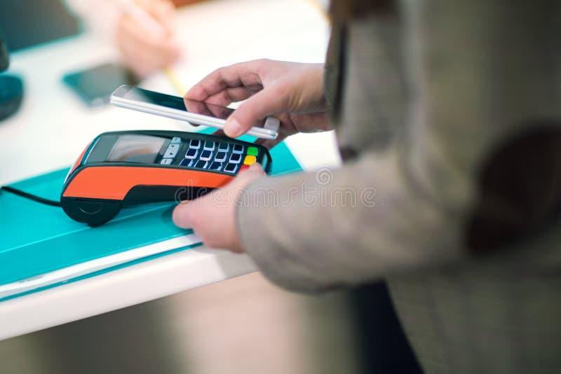 Άτομο που χρησιμοποιεί το κινητό τηλέφωνο για να πληρώσει στοκ φωτογραφία με δικαίωμα ελεύθερης χρήσης