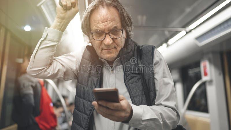 Άτομο που χρησιμοποιεί το κινητό τηλέφωνο στο τραίνο μετρό στοκ φωτογραφίες