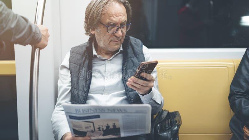 Άτομο που χρησιμοποιεί το κινητό τηλέφωνο στο τραίνο μετρό στοκ φωτογραφία