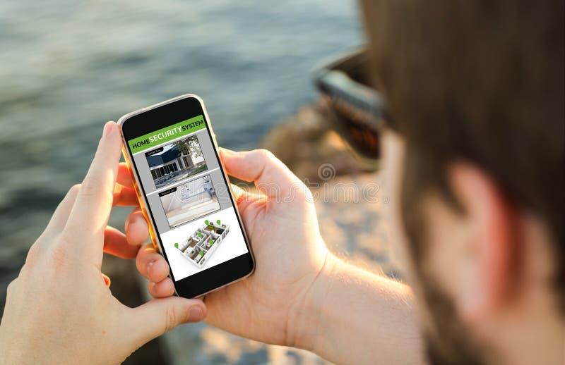 Άτομο που χρησιμοποιεί το κινητό τηλέφωνό του στην ακτή στον έλεγχο webcams στοκ εικόνα με δικαίωμα ελεύθερης χρήσης