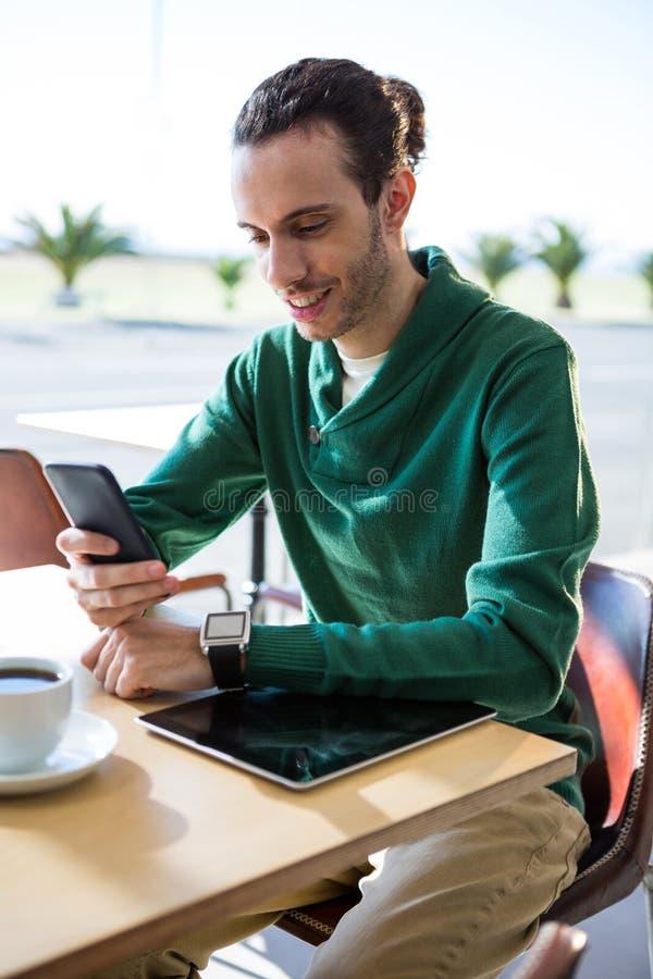 Άτομο που χρησιμοποιεί το κινητό τηλέφωνο με την ψηφιακή ταμπλέτα και το φλιτζάνι του καφέ στον πίνακα στοκ φωτογραφία