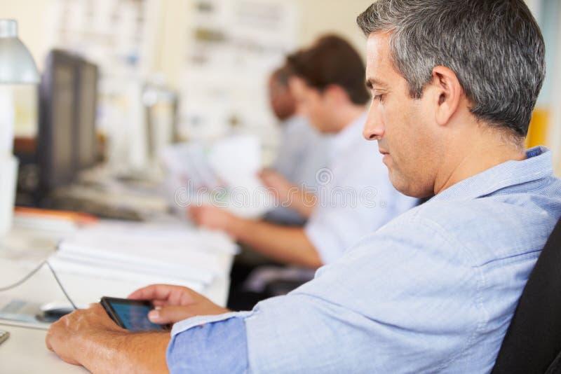 Άτομο που χρησιμοποιεί το κινητό τηλέφωνο στο γραφείο στο απασχολημένο δημιουργικό γραφείο στοκ φωτογραφίες