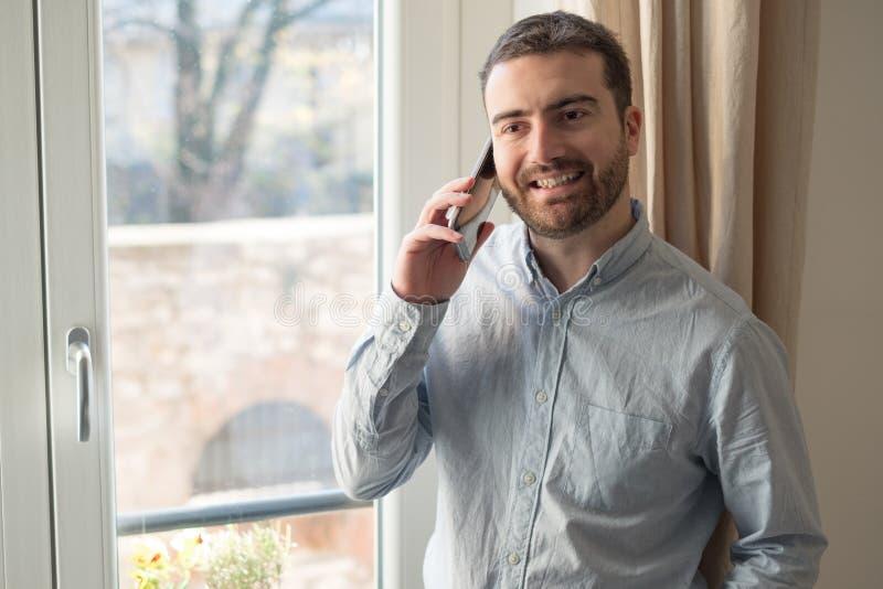 Άτομο που χρησιμοποιεί το κινητό τηλέφωνό του στο σπίτι στοκ φωτογραφία με δικαίωμα ελεύθερης χρήσης