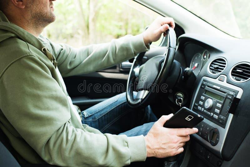 Άτομο που χρησιμοποιεί το τηλέφωνο οδηγώντας στοκ εικόνα