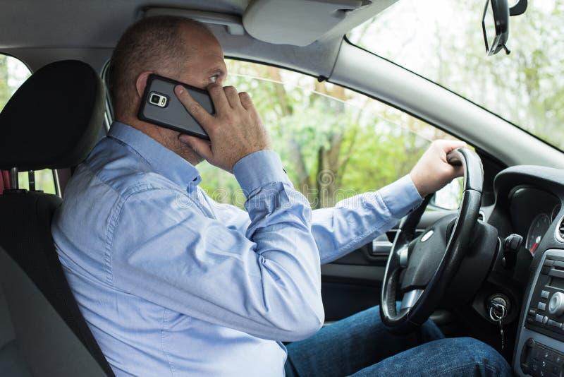 Άτομο που χρησιμοποιεί το τηλέφωνο οδηγώντας στοκ εικόνες