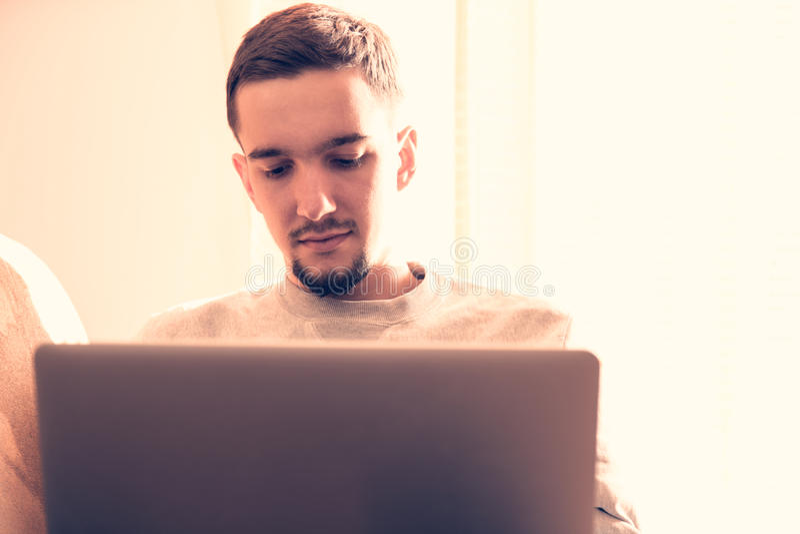 Άτομο που χρησιμοποιεί το φορητό προσωπικό υπολογιστή στο καθιστικό στοκ φωτογραφίες