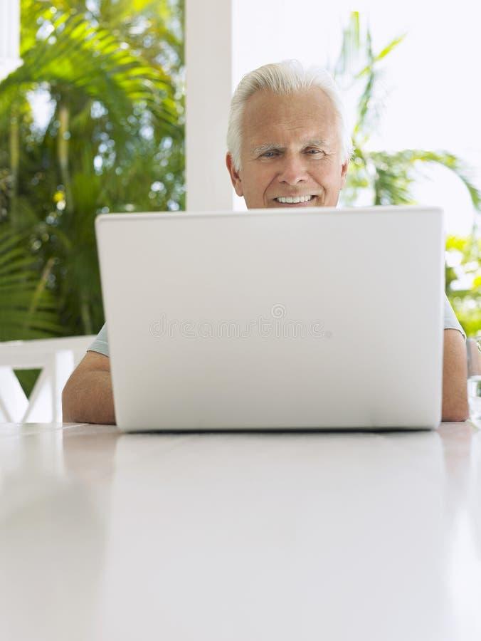 Άτομο που χρησιμοποιεί το lap-top στον πίνακα βεραντών στοκ εικόνες