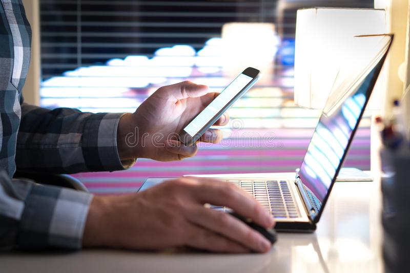 Άτομο που χρησιμοποιεί το smartphone και το lap-top αργά τη νύχτα στοκ εικόνα με δικαίωμα ελεύθερης χρήσης