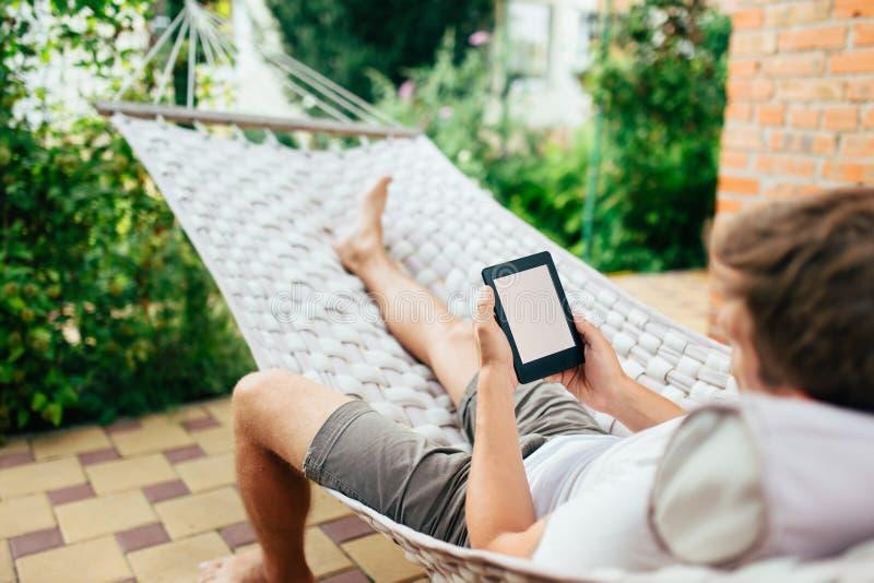 Άτομο που χρησιμοποιεί eBook ή υπολογιστής ταμπλετών χαλαρώνοντας σε μια αιώρα στοκ εικόνα