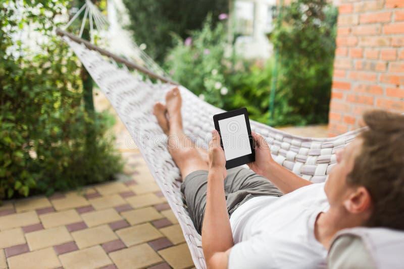 Άτομο που χρησιμοποιεί eBook ή υπολογιστής ταμπλετών χαλαρώνοντας σε μια αιώρα στοκ φωτογραφία
