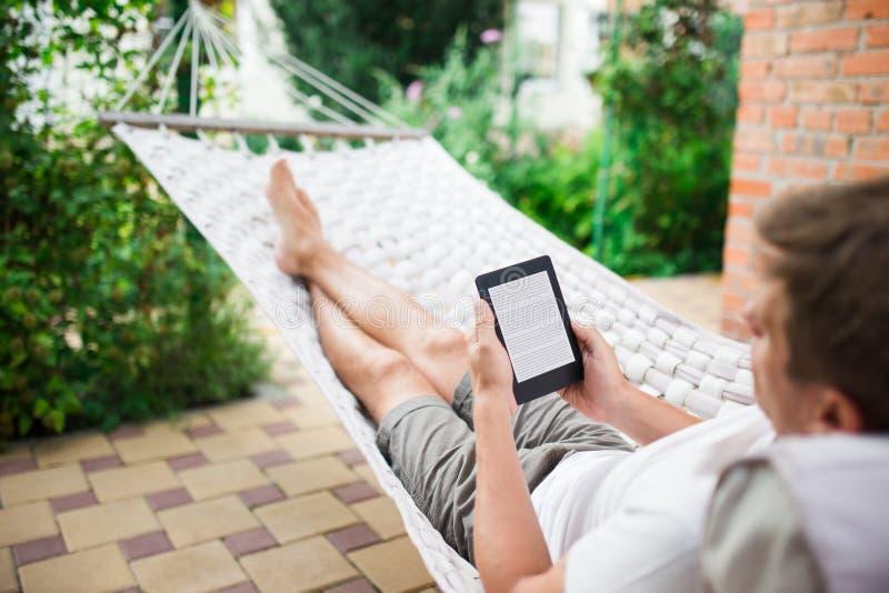 Άτομο που χρησιμοποιεί eBook με το κείμενο ipsum lorem στην οθόνη χαλαρώνοντας σε μια αιώρα στοκ φωτογραφία με δικαίωμα ελεύθερης χρήσης