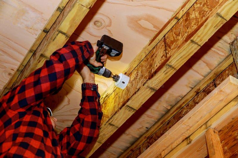 Άτομο που χτίζει ένα ξύλινο patio με τη σφυρηλάτηση βιδώνοντας μαζί τις ακτίνες στοκ φωτογραφία