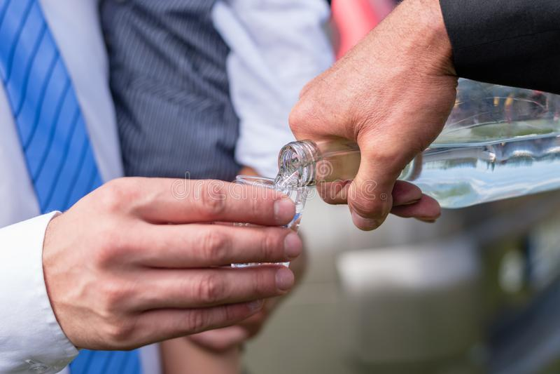 Άτομο που χύνει το σπιτικό κονιάκ δαμάσκηνων σε έναν τσεχικό γάμο στοκ εικόνα με δικαίωμα ελεύθερης χρήσης