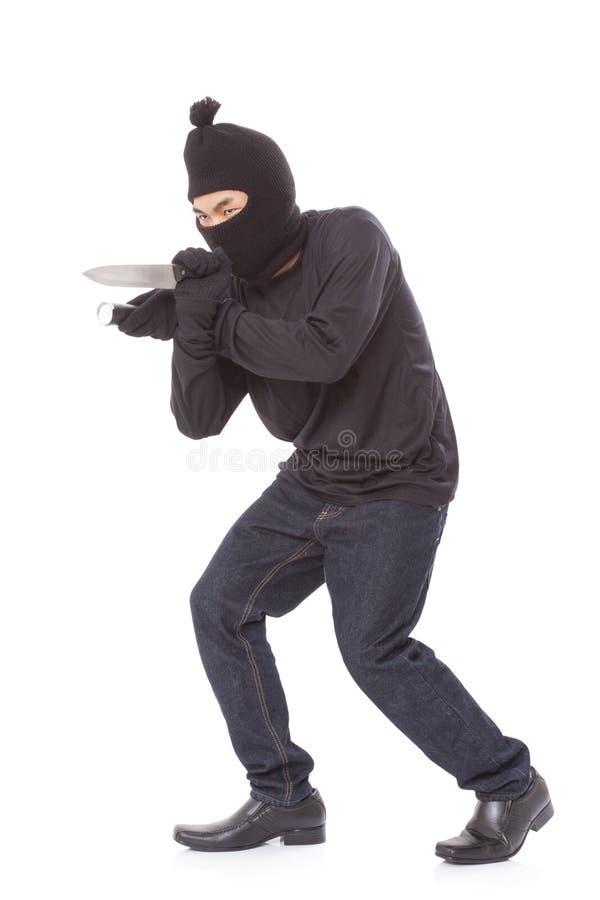 Άτομο σε έναν φακό εκμετάλλευσης μασκών με ένα μαχαίρι στοκ φωτογραφία με δικαίωμα ελεύθερης χρήσης