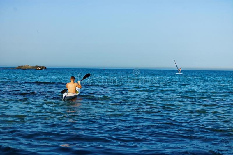 Άτομο σε ένα κανό στη θάλασσα, Kayaking, κωπηλασία σε κανό στοκ εικόνα