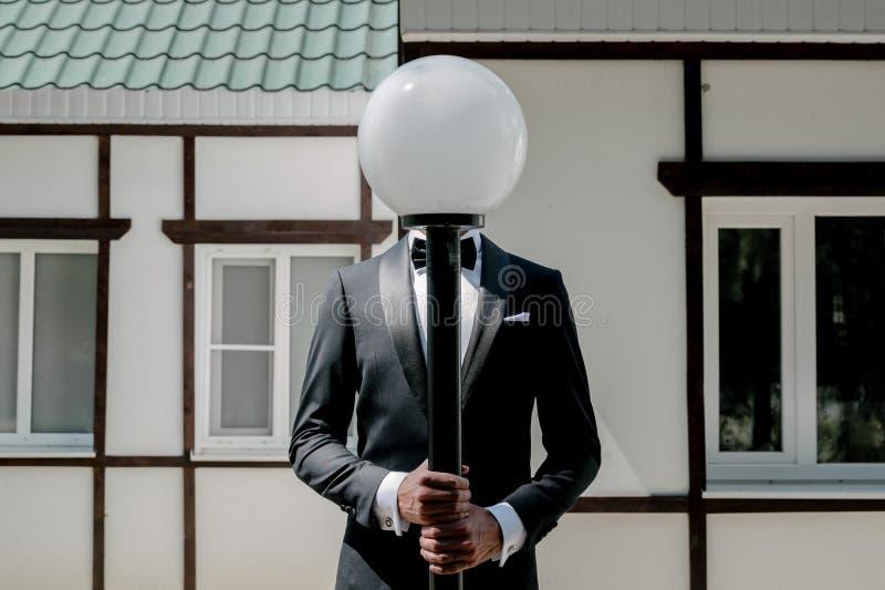 Άτομο σε ένα μαύρο κοστούμι και λευκός μαύρου δεσμός πουκάμισων και σε ένα μαύρο υπόβαθρο Χωρίς ένα πρόσωπο στοκ εικόνες με δικαίωμα ελεύθερης χρήσης