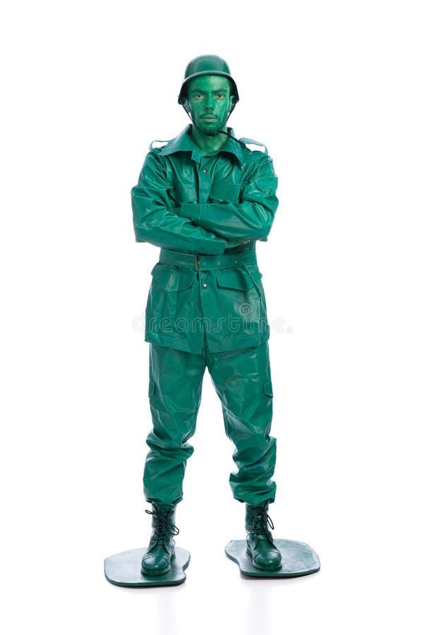 Άτομο σε ένα πράσινο κοστούμι στρατιωτών παιχνιδιών στοκ εικόνα