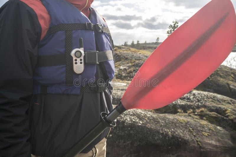 Άτομο σε ένα σακάκι ζωής με walkie-talkie και μια στάση κουπιών στοκ φωτογραφία με δικαίωμα ελεύθερης χρήσης