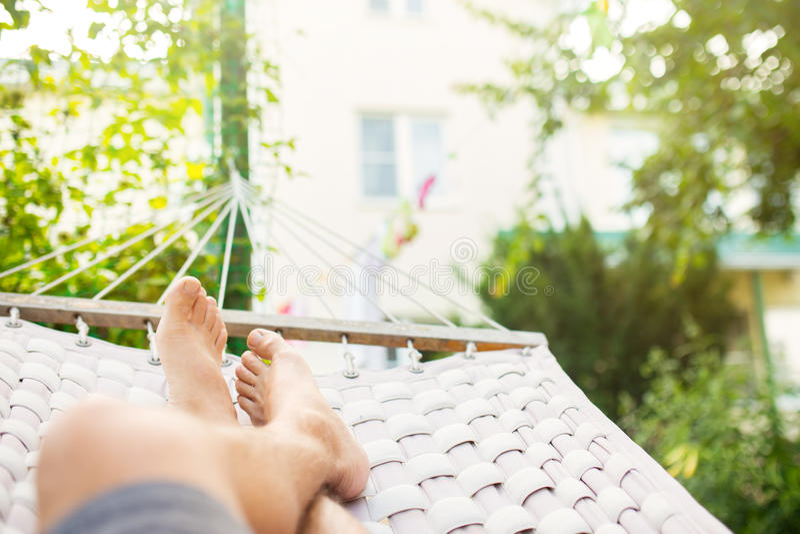 Άτομο σε μια αιώρα μια θερινή ημέρα στοκ εικόνες
