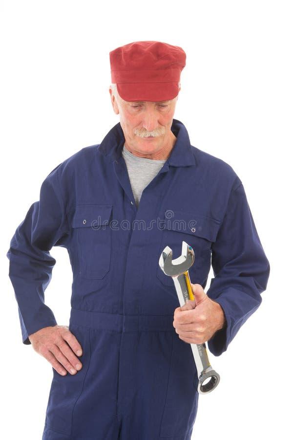 Άτομο σε μπλε συνολικά με το γαλλικό κλειδί στοκ φωτογραφίες