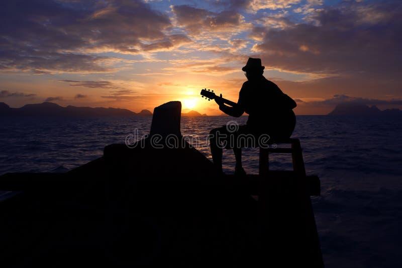 Άτομο σκιαγραφιών που παίζει μια κιθάρα στη βάρκα με τα sunris μπλε ουρανού στοκ εικόνα