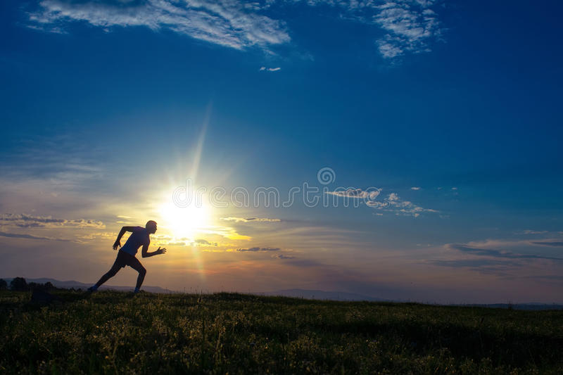 Άτομο σκιαγραφιών που τρέχει στο λιβάδι στοκ εικόνες
