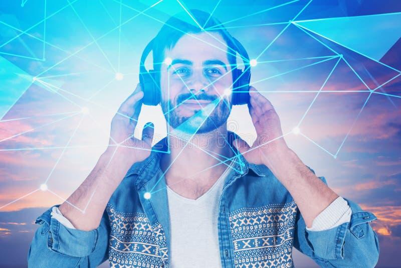 Άτομο στα ακουστικά πέρα από τα σύννεφα, ολόγραμμα δικτύων στοκ φωτογραφία με δικαίωμα ελεύθερης χρήσης