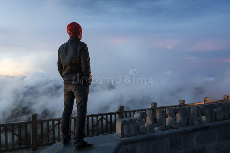 άτομο στα βουνά που εξετάζουν την απόσταση Νέος ταξιδιώτης που στέκεται και που εξετάζει την άποψη της φύσης σε Sapa Βιετνάμ σε β στοκ φωτογραφία