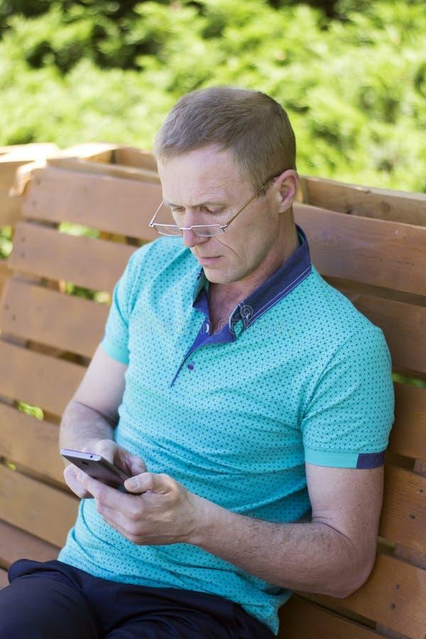 Άτομο στα γυαλιά με το τηλέφωνο στοκ φωτογραφίες