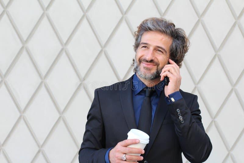 Άτομο στα επιχειρησιακά ενδύματα που κρατά το φλυτζάνι και το smartphone καφέ στοκ εικόνες με δικαίωμα ελεύθερης χρήσης