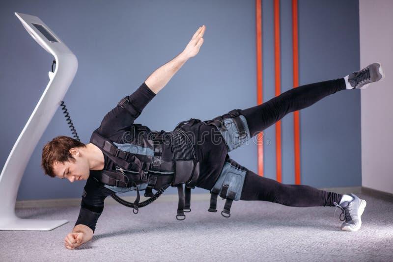 Άτομο στα ηλεκτρικά μυϊκά κοστούμια υποκίνησης που κάνουν τη δευτερεύουσα άσκηση σανίδων EMS στοκ εικόνα
