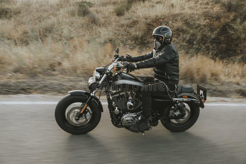Άτομο στα μαύρα ενδύματα που οδηγούν μια μαύρη κλασική αμερικανική μοτοσικλέτα στοκ φωτογραφία με δικαίωμα ελεύθερης χρήσης
