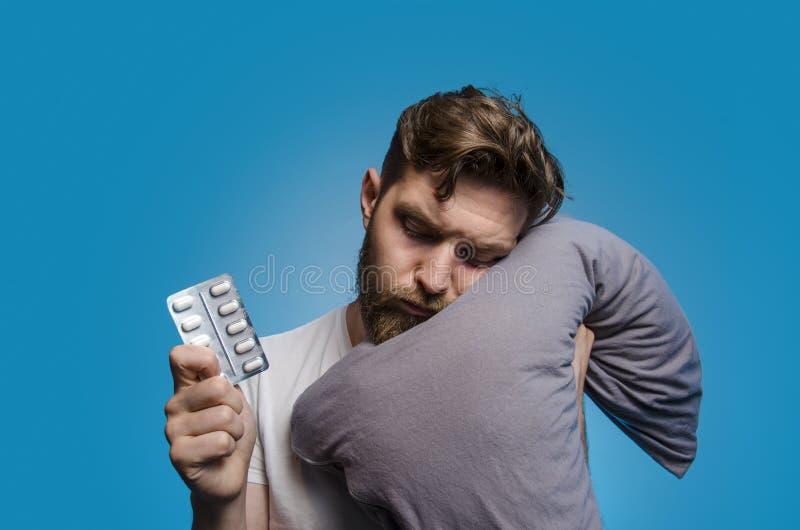 Άτομο στα μπλε χάπια μαξιλαριών και ύπνου εκμετάλλευσης υποβάθρου στοκ εικόνα με δικαίωμα ελεύθερης χρήσης