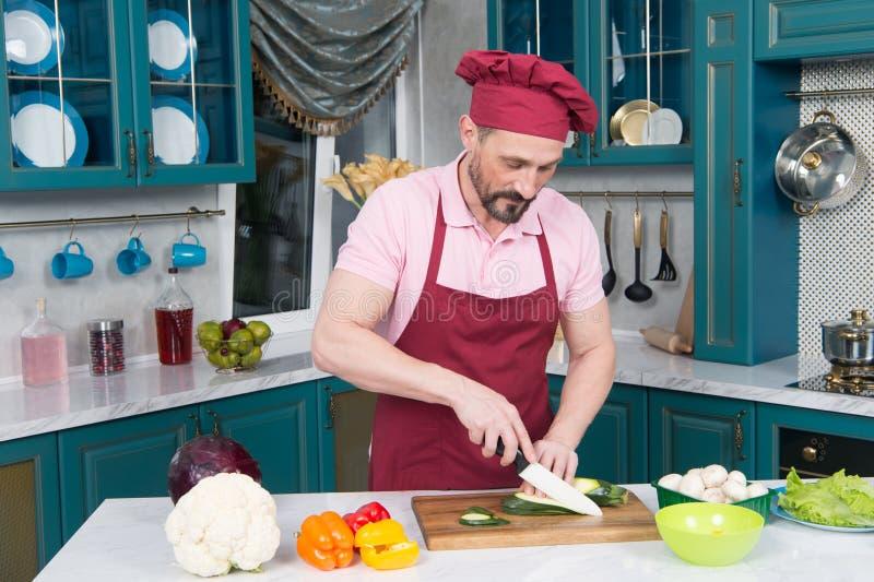 Άτομο στα ομοιόμορφα τέμνοντα κολοκύθια ποδιών στη φέτα από το μαχαίρι Πορτοκαλιά και κόκκινη πάπρικα στον πίνακα που προετοιμάζε στοκ εικόνα