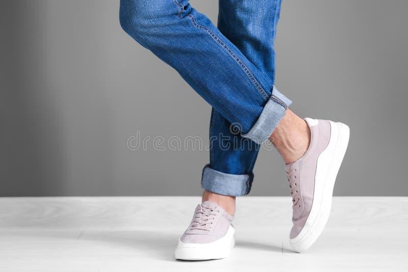 Άτομο στα περιστασιακά παπούτσια κοντά στον τοίχο στοκ φωτογραφίες