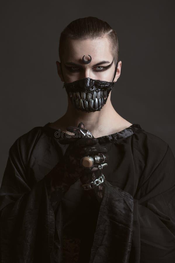 Άτομο στα σκοτεινά ενδύματα, daemon στοκ εικόνες