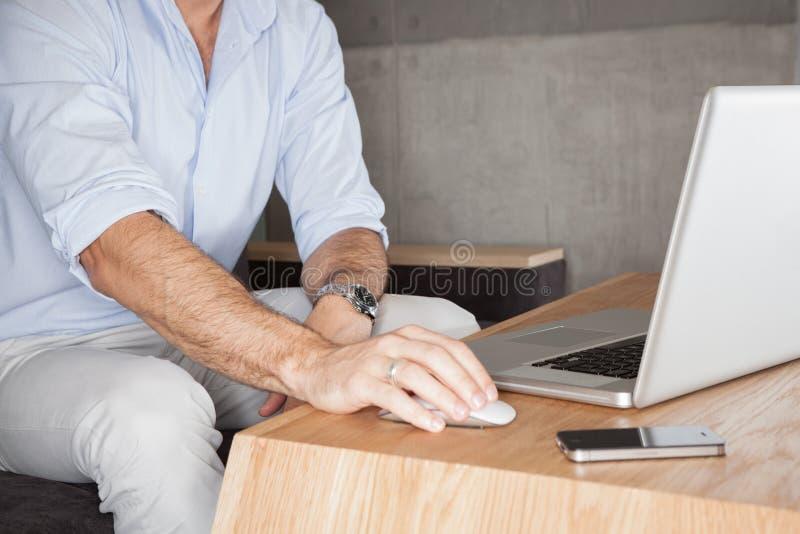 Άτομο στην αρχή με το lap-top στοκ εικόνα