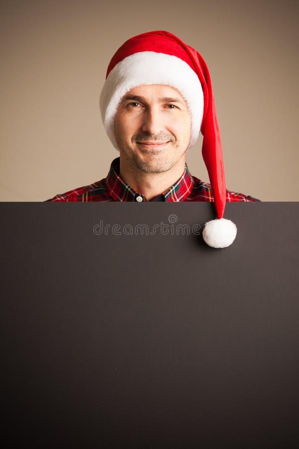 Άτομο στην αφίσσα εκμετάλλευσης καπέλων Χριστουγέννων santa στοκ φωτογραφία