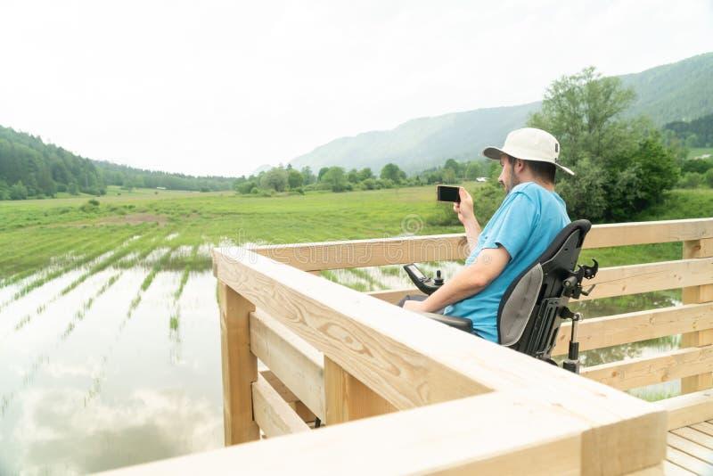 Άτομο στην ηλεκτρική αναπηρική καρέκλα που χρησιμοποιεί τη κάμερα smartphone κοντά στη λίμνη στη φύση στοκ εικόνα με δικαίωμα ελεύθερης χρήσης